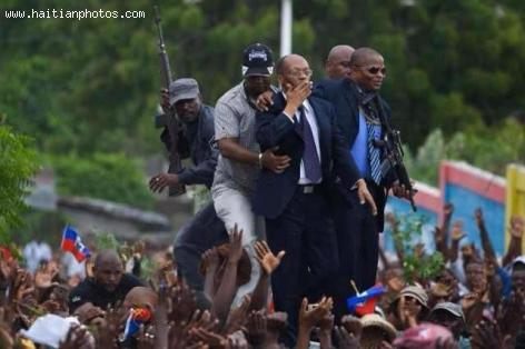 Jean Bertrand Aristide blowing kisses from the rooftop of his SUV