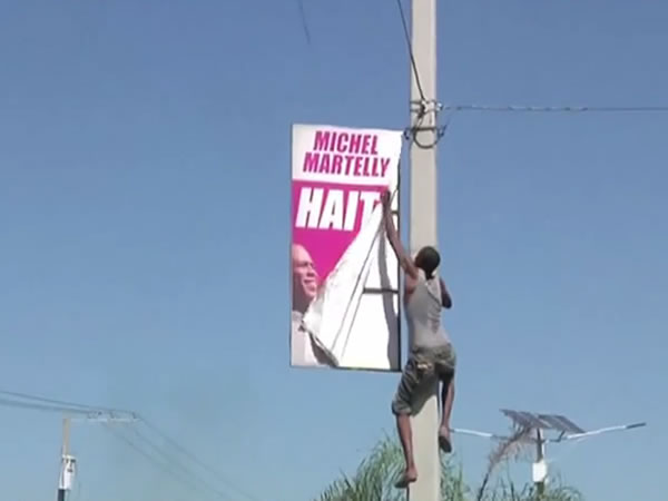 Street Protester removing Sign of President Michel Martelly