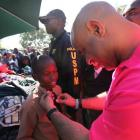 Prime Minister Laurent Lamothe fixing the Tie of a young Child