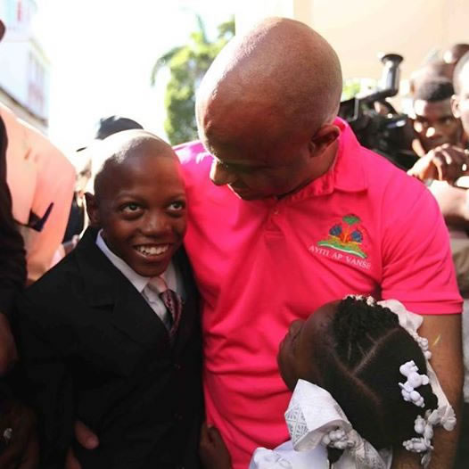 Prime Minister Laurent Lamothe talking with two young children