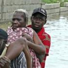 Haitian woman being carried as her house flooded
